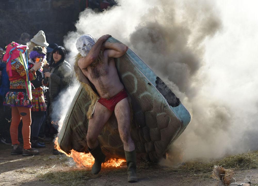 Participante carrega um colchão ardendo durante o antigo carnaval de Zubieta, na comunidade autônoma espanhola de Navarra
