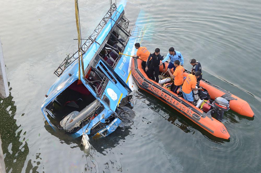 Policiais indianos resgatam pessoas após o acidente com um ônibus no canal de Ghogra