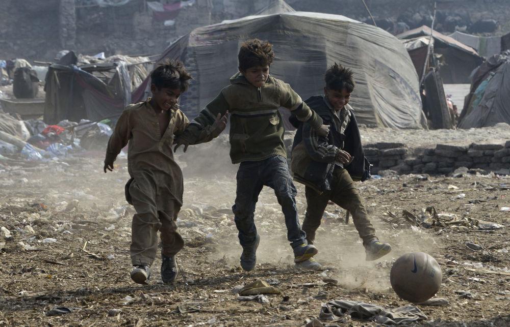 Crianças paquistanesas jogam futebol em uma favela no Paquistão