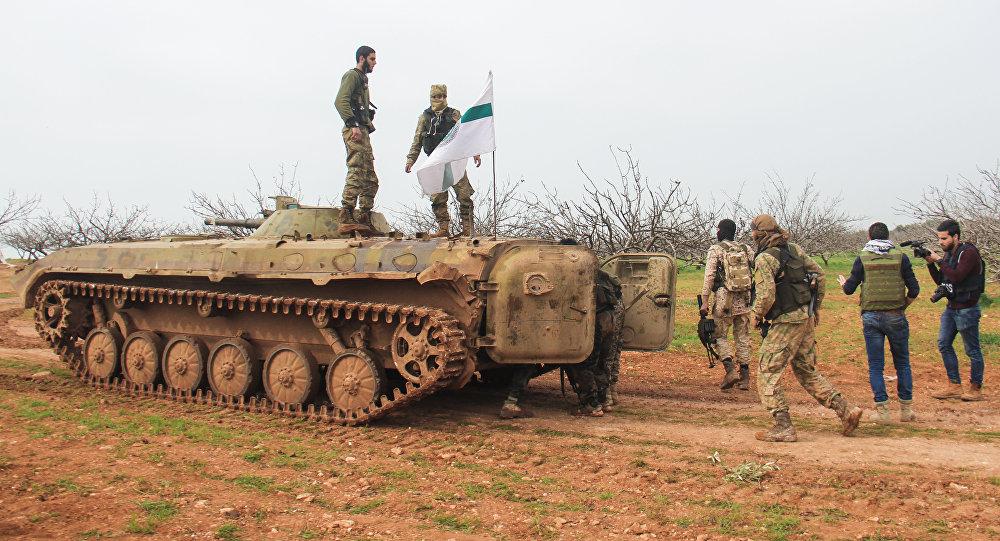 Foto de 22 de março de 2017 tirada na região da cidade de Maardes, na Síria, mostra rebeldes carregando a bandeira do Tahrir al-Shamn province of Hama, shows rebel fighters walking past an armoured vehicle carrying the flag of the Tahrir al-Sham rebel alliance