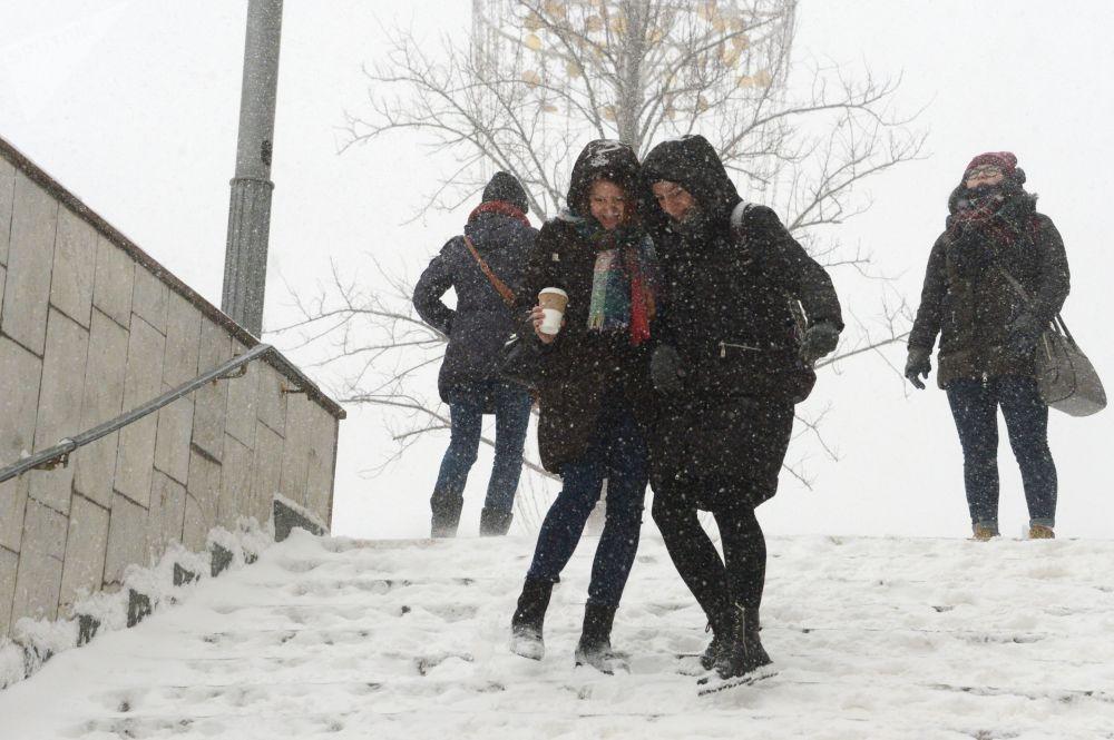 Moças descem as escadas do metrô durante nevada, Moscou