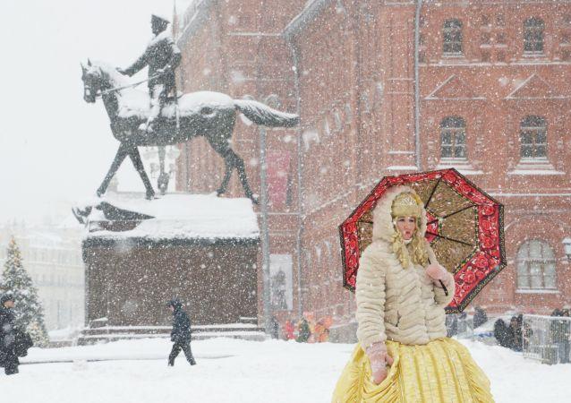 Mulher usa guarda-chuva para se proteger da nevada na Praça do Manege, no centro de Moscou