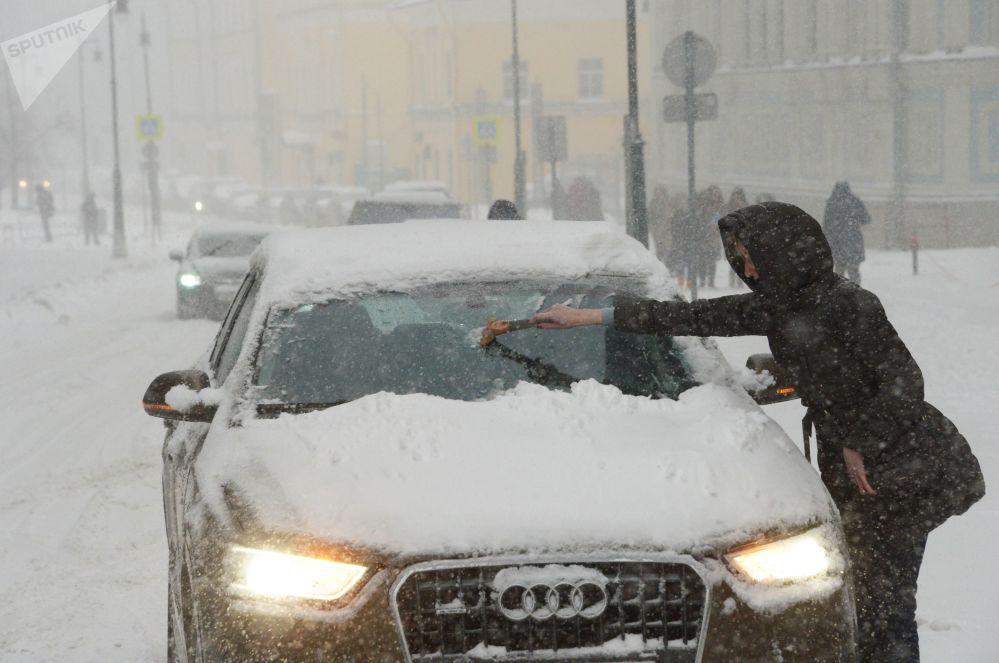 Motorista tenta limpar seu carro coberto de neve que caiu em quantidades recordes nos últimos dias