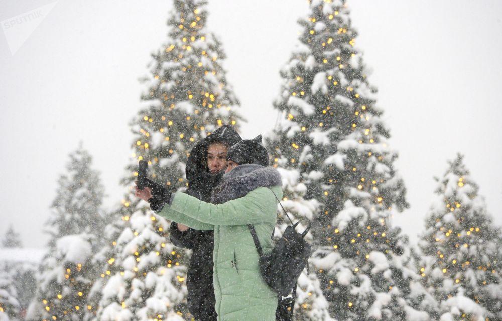 Moças posam para foto durante nevada na Praça do Manege, no centro de Moscou