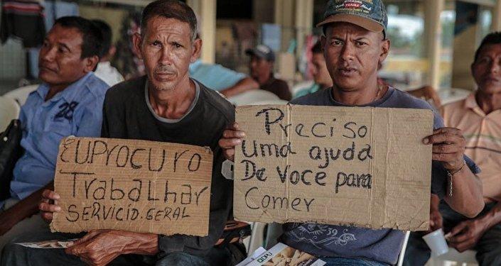 Migrantes venezuelanos seguram de cartazes à procura de trabalho na cidade brasileira de Boa Vista, estado de Roraima, outubro de 2017.