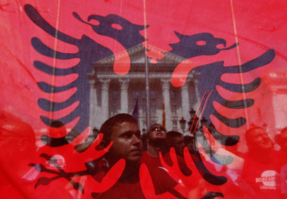 Manifestantes antigovernamentais vistos através da bandeira albanesa protestam em frente do prédio do governo.