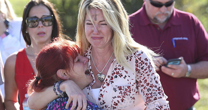 Mulheres choram após tiroteio em escola na Flórida.