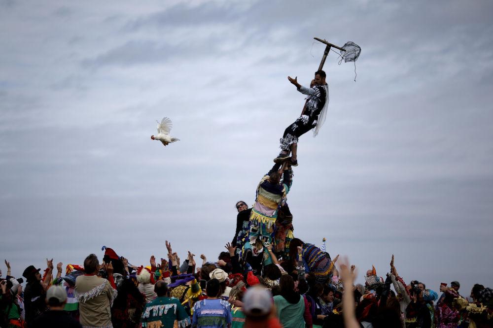 Participante de uma festa Faquetigue Courir de Mardi Gras larga uma galinha da gaiola em Eunice, na Louisiana, EUA