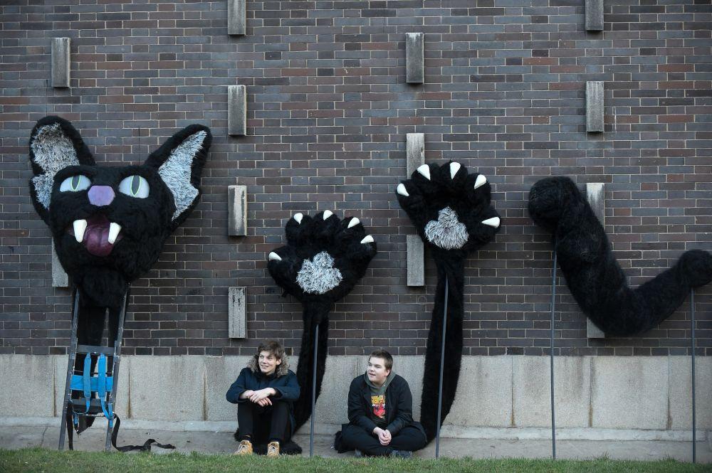 Dois jovens junto a figuras de gatos em tecido esperam pelo começo do festival Zizkov Carnival, em Praga