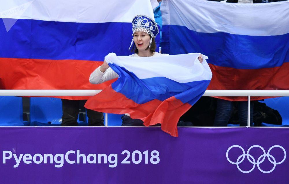 Torcedora apoia os atletas da patinação artística russos Yevgenia Tarasova e Vladimir Morozov