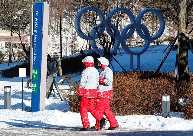 Voluntários caminham ao lado dos anéis olímpicos no resort Alpensia em Pyeongchang, Coreia do Sul