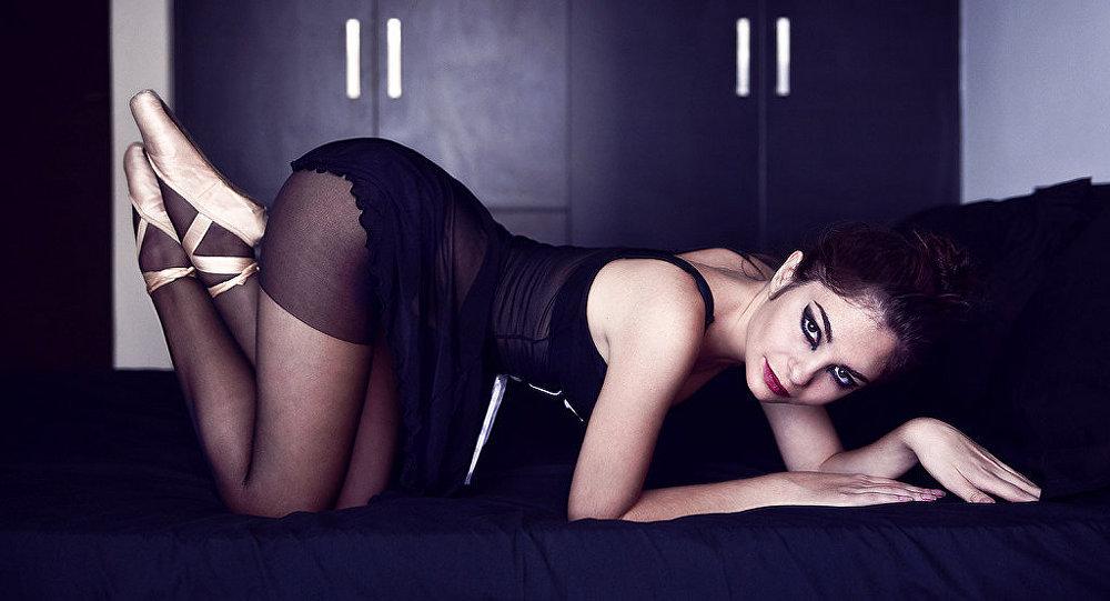 Jovem posando sensualmente na cama