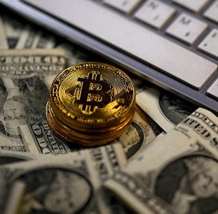 Bitcoin sobre dólares próximo ao teclado do computador