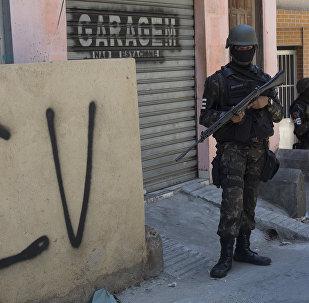 Militar na Rocinha ao lado de muro com as inscrições do Comando Vermelho.