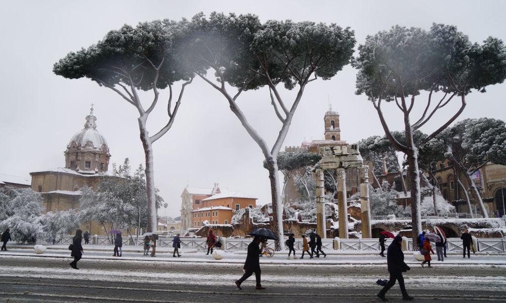 Pessoas caminham por Roma coberta de neve