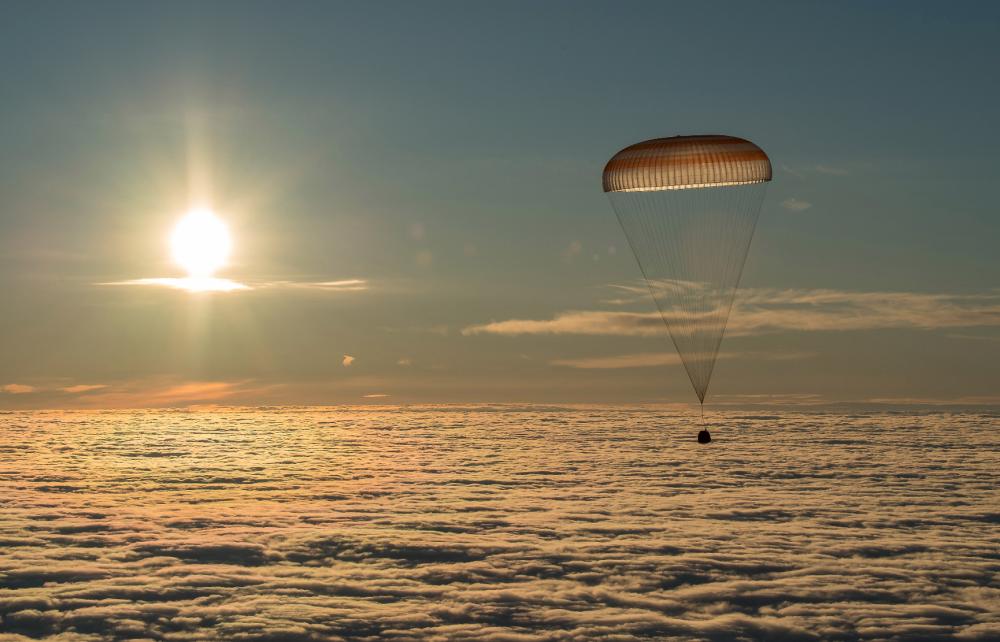 Cápsula da nave Soyuz MS-06 descendo em paraquedas com cosmonautas da Estação Espacial Internacional (EEI)