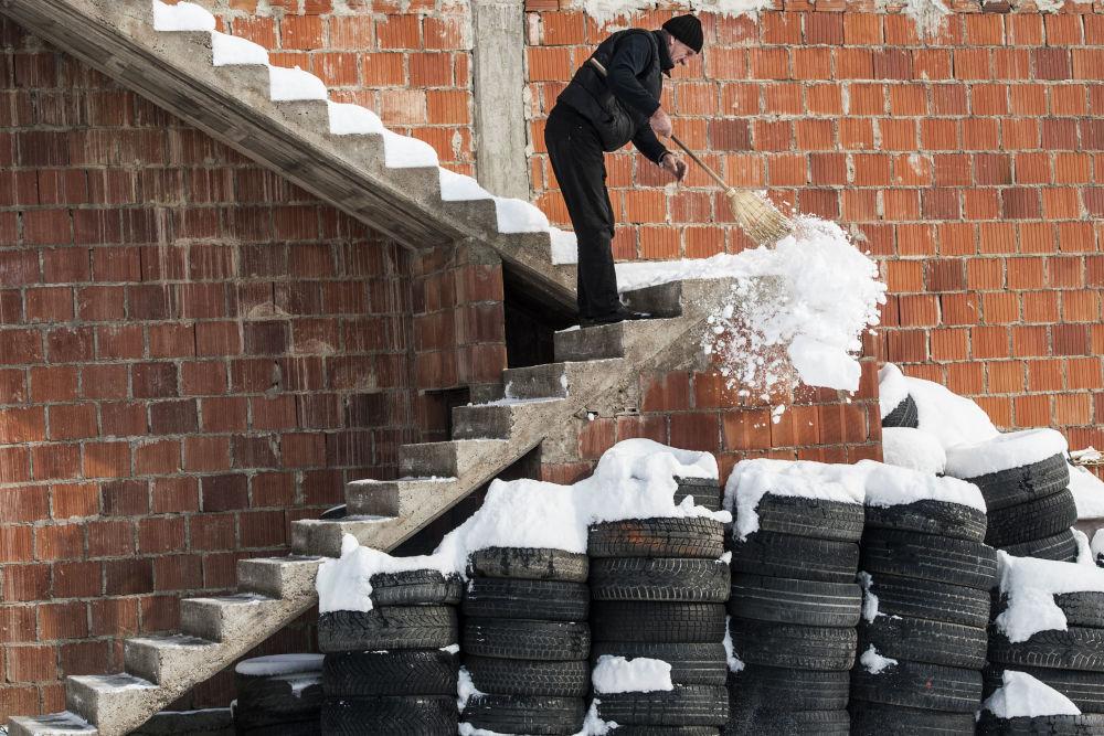Um homem limpa a escada da neve na aldeia Mramor, perto de Pristina