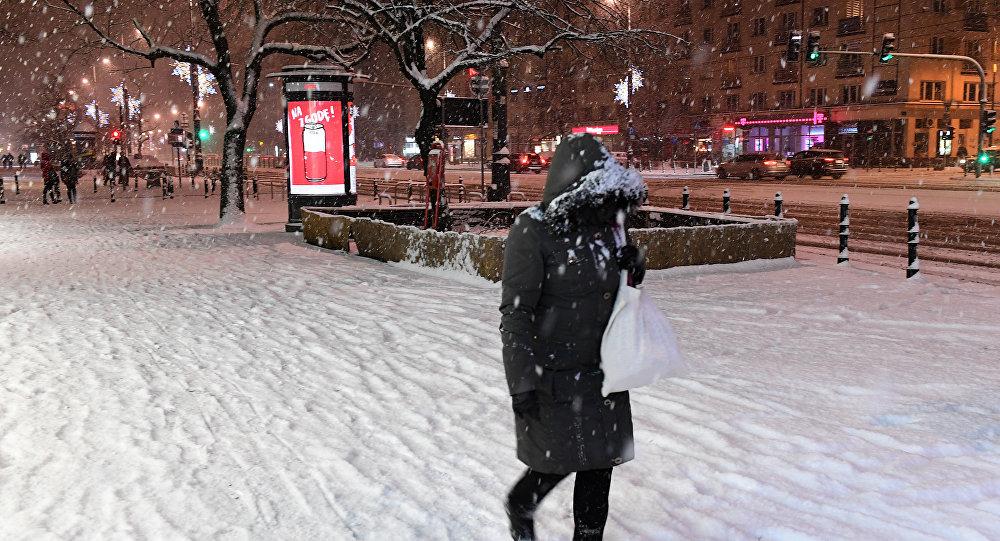 Uma foto tirada em 5 de fevereiro de 2018 mostra um pedestre caminhando na rua coberto de neve na capital polonesa, Varsóvia