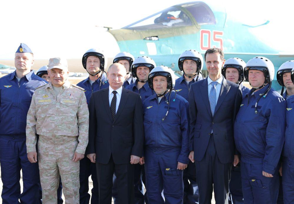 Vladimir Putin, o presidente sírio Bashar Assad e o ministro da Defesa russo Sergei Shoigu, fotografados junto a militares russos durante uma visita à base russa de Hmeymim, em 11 de dezembro de 2017