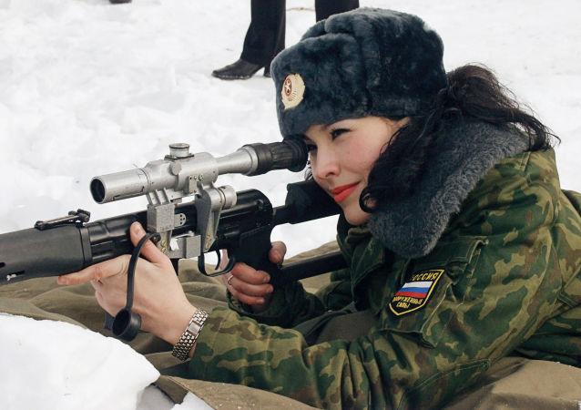 Participante da etapa final do concurso nacional Beleza com Platinas da Rússia fazendo fogo com fuzil de precisão