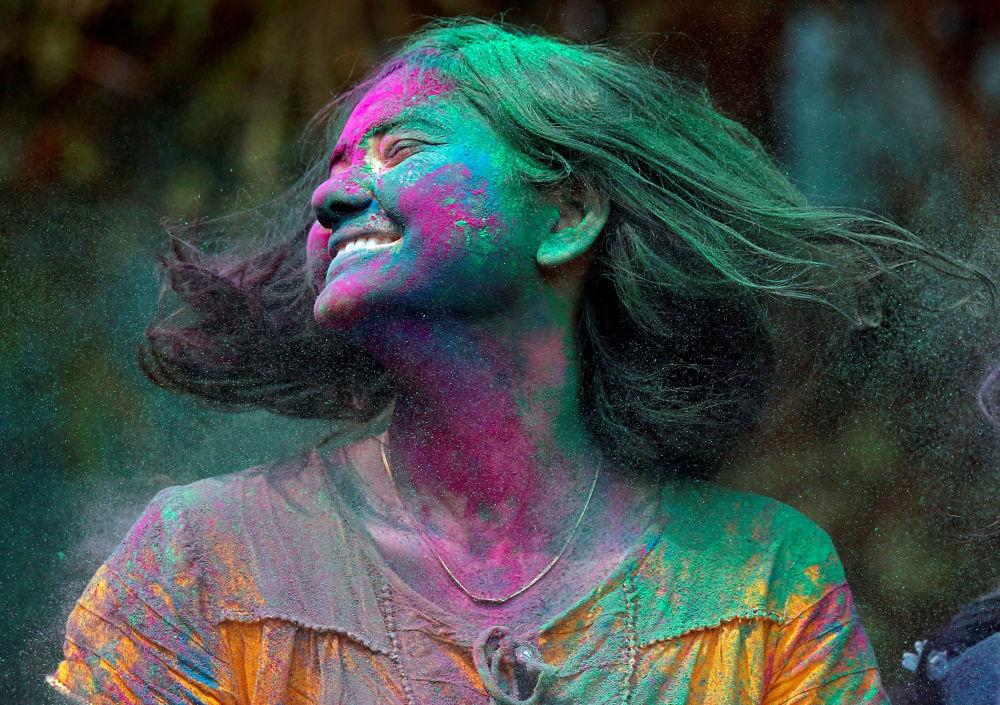 Mulher coberta com pós coloridos durante os festejos do tradicional festival Holi, na Índia