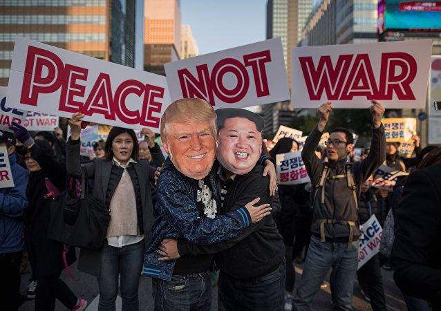 Manifestantes vestidos como o líder norte-coreano Kim Jong-Un e o presidente dos EUA, Donald Trump se abraçam durante um comício pela paz em Seul.