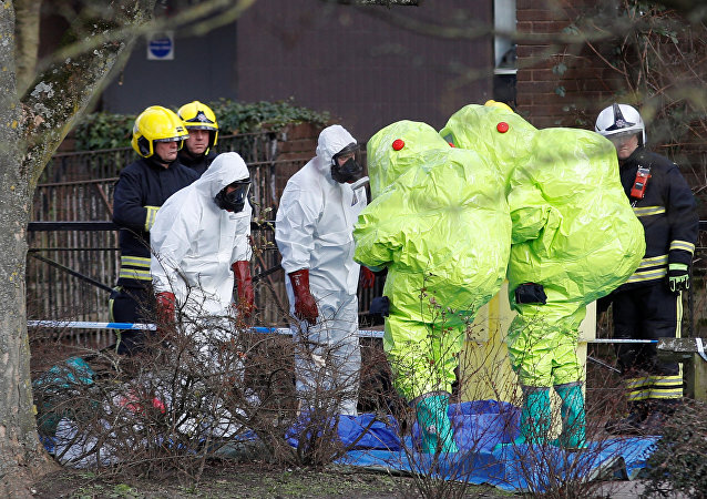 Officials in protective suits check their equipment before repositioning the forensic tent, covering the bench where Sergei Skripal and his daughter Yulia were found, in the centre of Salisbury, Britain, March 8, 2018