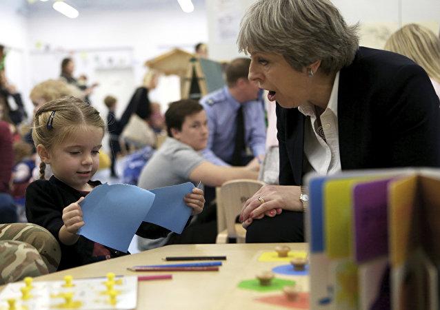 Theresa May, primeira-ministra do Reino Unido, fala com uma criança no jardim de infância durante uma visita a uma das duas bases militares britânicas no mediterrâneo do leste, na ilha de Chipre.