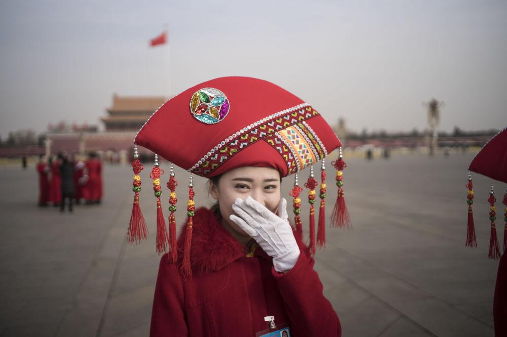 Moça da equipe de hospitalidade durante o Congresso Nacional do Povo, na Praça Tiananmen em Pequim, China