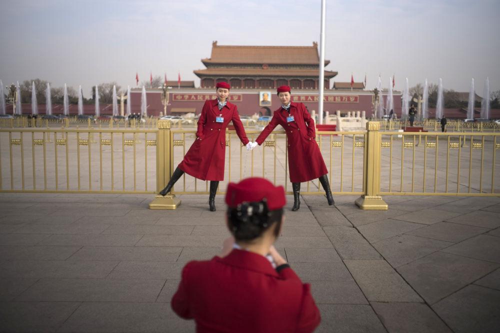 Moças da equipe de hospitalidade posam para fotos durante o Congresso Nacional do Povo, na Praça Tiananmen em Pequim, China