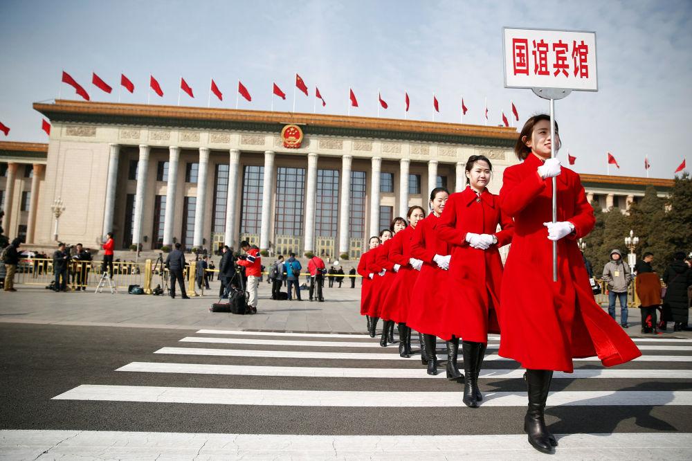 Moças da equipe de hospitalidade perto do Grande Salão do Povo, onde decorre o Congresso Nacional do Povo, na Praça Tiananmen em Pequim, China