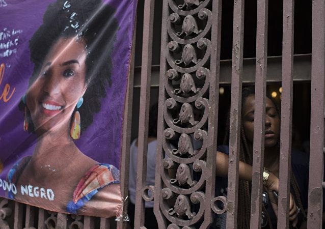 Mulher perto de cartaz de vereadora Marielle Franco, Rio de Janeiro