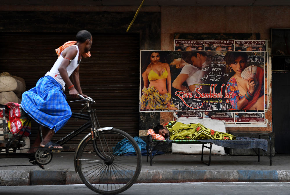 Ciclista hindu passa por homem sem teto, Kolkata, Índia