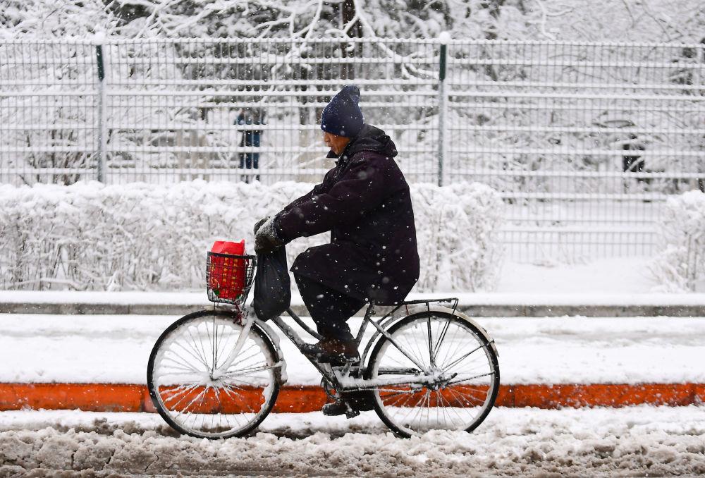 Homem andando de bicicleta durante nevasca na cidade chinesa de Shenyang