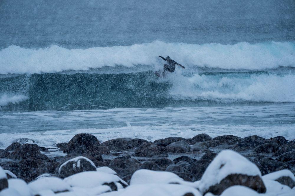 Surfista na onda, arquipélago Lofoten, Noruega