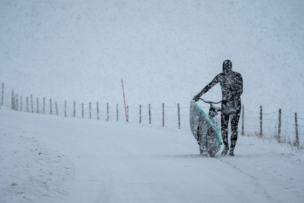 Surfista caminha durante nevasca, arquipélago Lofoten, Noruega
