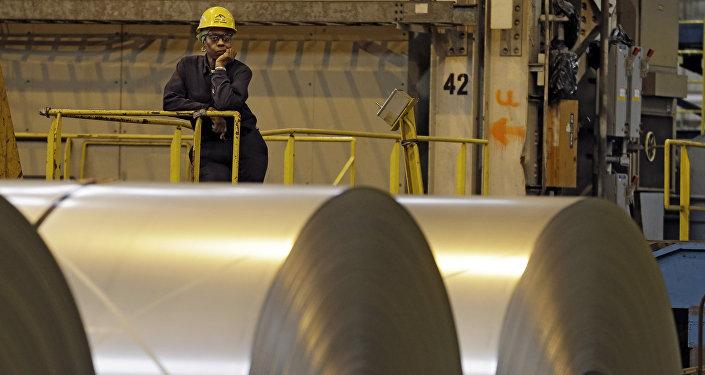 Operário olha detrás de rolos de aço enquanto secretário do trabalho, Seth Harris, fala com trabalhadores em Cuyahoga Height, Ohio.
