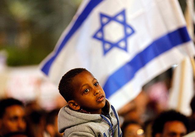 Um menino participa do protesto em Tel Aviv, Israel, contra o plano do governo de deportar imigrantes africanos.