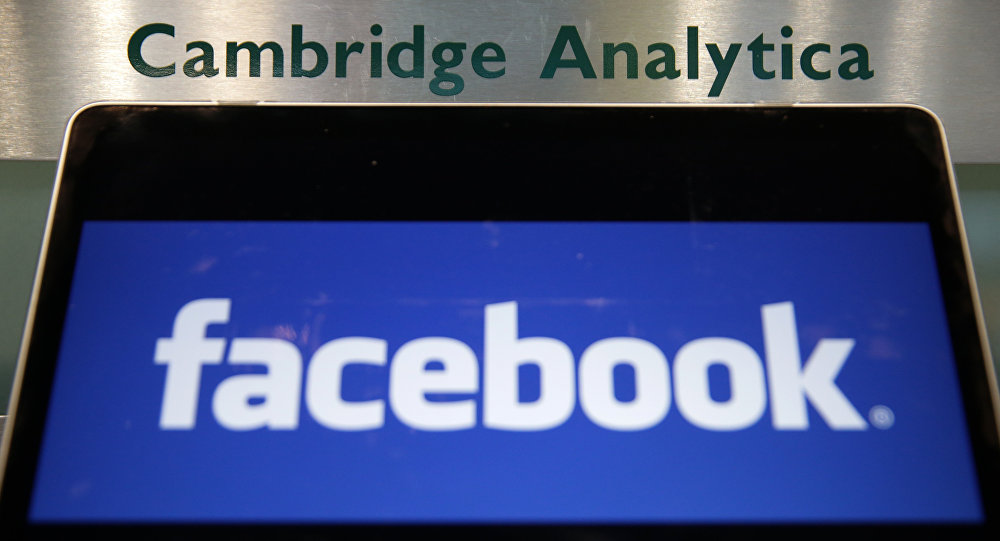 Laptop mostrando logotipo do Facebook é mantido ao lado de uma placa da Cambridge Analytica na entrada do prédio que abriga os escritórios da Cambridge Analytica, no centro de Londres.