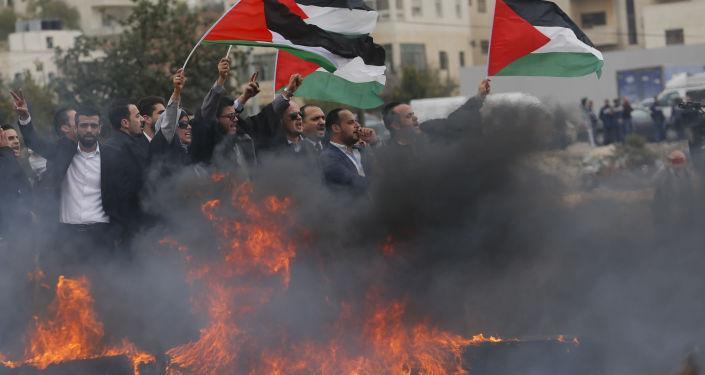 Um grupo de advogados palestinos segura bandeiras nacionais durante um protesto contra a decisão de Donald Trump de reconhecer Jerusalém como capital do Estado judeu, em 13 de dezembro de 2017
