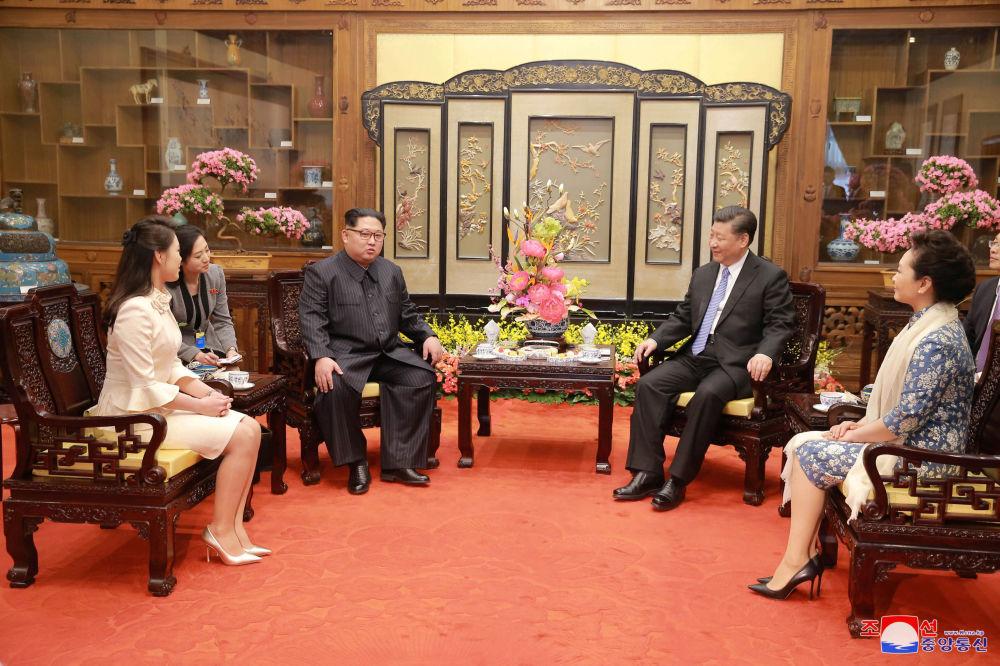 Líder da Coreia do Norte, Kim Jong-un, junto com sua esposa, Ri Sol Ju, encontra-se com o presidente chinês, Xi Jiping, e sua esposa Peng Liyuan, em Pequim, no âmbito da visita entre 25 e 28 de março de 2018