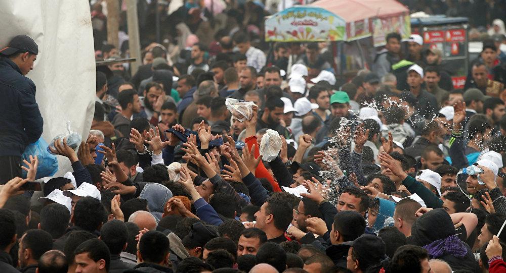 Os palestinos recebem comida durante um protesto na cidade de barracas ao longo da fronteira de Israel com Gaza, exigindo o direito de retornar à sua terra natal, a leste da cidade de Gaza