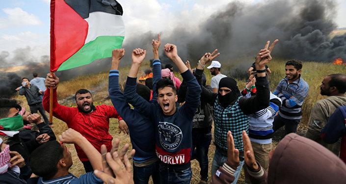 Palestinos gritam contra tropas israelenses durante protesto na Faixa de Gaza. Ao menos 15 pessoas foram mortas e 1.200 ficaram feridas.