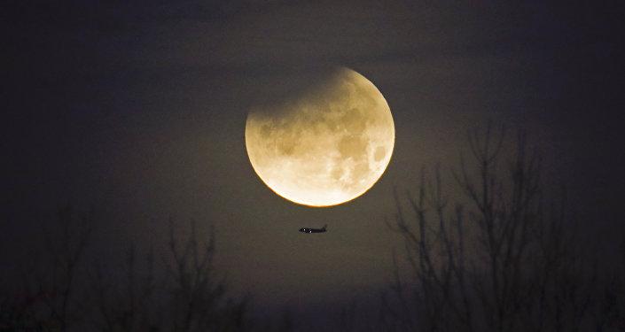 Avião com Lua no plano de fundo durante fenômeno raríssimo que combina Superlua, Lua azul e eclipse lunar
