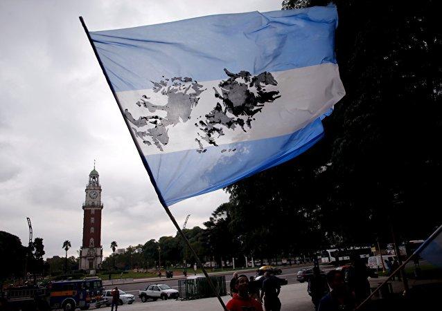 Homem segurando bandeira argentina com imagem das ilhas Malvinas