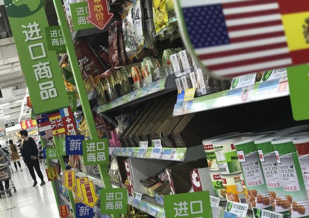 Mulheres em um supermercado de Pequim passando pelas prateleiras de produtos importados dos EUA e de outros países, 2 de abril de 2018