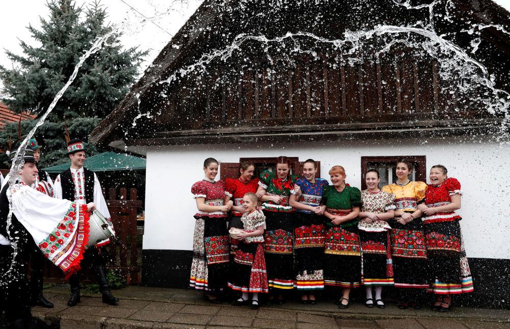 Homens lançam água durante os festejos tradicionais da Páscoa, na Hungria