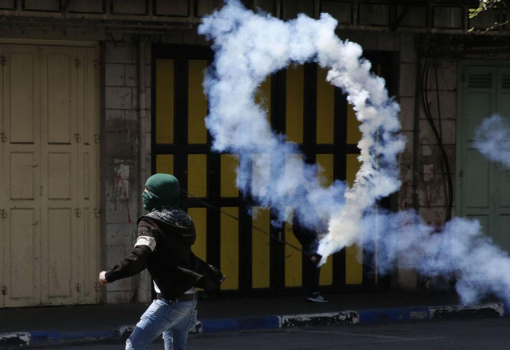 Manifestante palestino atira uma botija de gás lacrimogêneo contra os soldados israelenses na cidade de Hebron