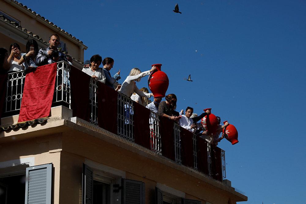 Pessoas se preparam para jogar fora potes de barro de janelas no âmbito da tradição grega de Botides, no Sábado Santo, na Grécia