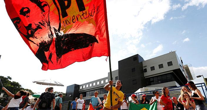 Apoiador do ex-presidente Lula segura bandeira com rosto do petista em Curitiba